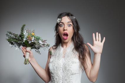 Surprised bride holding flowers bouquet